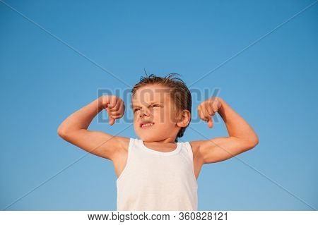 Strong Little Boy In White Tank Top Showing Strong Muscle On Blue Sky Background