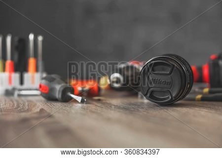 Nikon Lens In Repair Against The Background Of A Pile Of Tools Russia. Moscow April 10, 2020