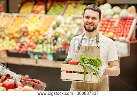 Waist Up Portrait Of Bearded Man Holding Box Of Vegetables And Smiling At Camera While Selling Fresh