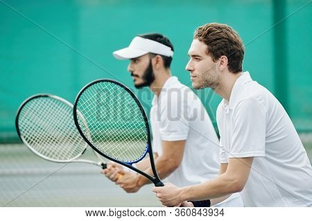 Side View Of Serious Concentrated Tennis Players With Rackets Ready To Play