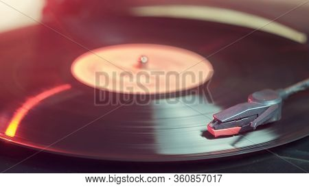 Retro Record Player With A Spinning Black Vinyl Record Reflecting Red Light