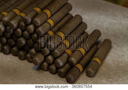Cuban Cigars Close Up On Wooden Table. Side View Of A Cigars Bunch. Handmade Cigars In The Shop.
