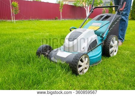 A Lawn Mover Is Cutting Green Grass, The Gardener Is Working With A Lawn Mower, A Close-up, The Yard