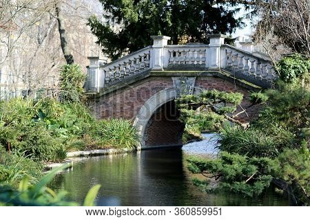 Beautiful Old Stone Bridge With Railing Over Clean River In Preserve. Natural Nature Consisting Of A
