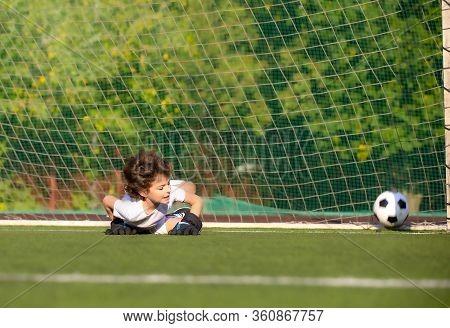 Junior Soccer Goalkeeper. Disappointed Boy In White Goalie Sportswear. Goalkeeper Missed A Goal Duri