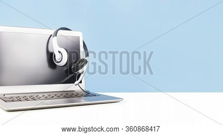 Laptop With Blank Screen With Headphones On White Desk Blue Background And Copy Space. Distant Learn