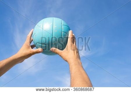 A Close-up Of Men's Hands With A Volley Ball Against The Blue Sky.  Sport Games.
