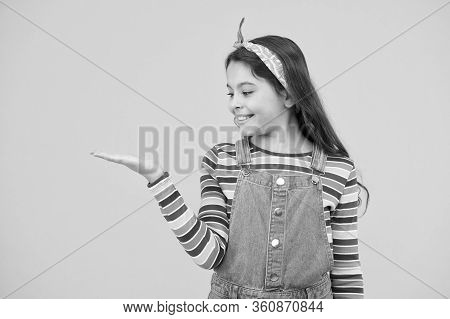 Product Presentation. Kid Happy Smiling Face Show Something On Open Palm Copy Space Yellow Backgroun