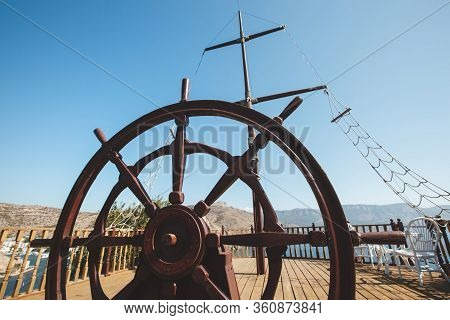 Rudder Of An Old Wooden Sailing Boat. Steering Wheel Of A Retro Vintage Ship.