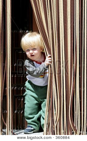 Young Boy With Blond Or Blonde Hair And Blue Eyes Looking Out From Behind Curtain