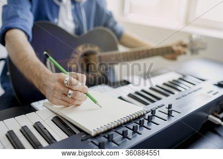 Male Music Arranger Composing Song On Midi Piano And Audio Equipment In Digital Recording Studio. Ma