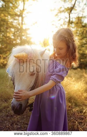 Girl In Purple Dress Hugging White Unicorn Horse. Dreams Come True. Fairy Tale.