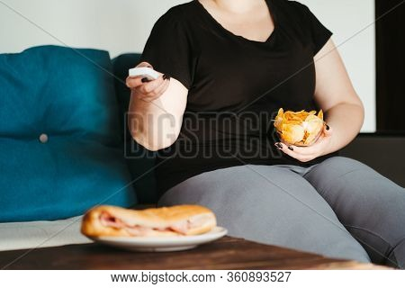 Mindless Snacking, Home Sedentary Lifestyle, Compulsive Overeating. Obese Lazy Woman Sitting On Sofa