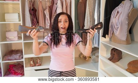 Portrait Of Young Shocked Woman, Holding Shoes In Her Hands In Dressing Room. Charming Female Ponder