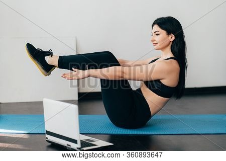 Home Training, Fitness, Motivation Concept. Young Fit Woman Doing Sport Exercises With Online Guide