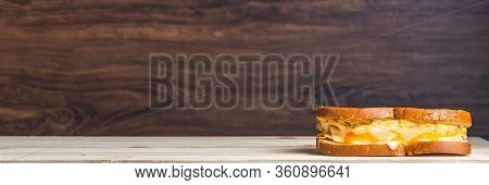 Far Right Justified Grilled Cheese Sandwich On Dark Wood Backdrop