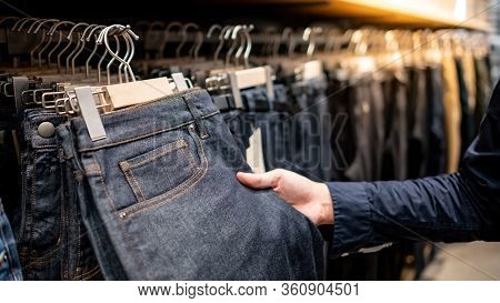 Male Hand Customer Choosing Black Men Jeans Or Denim Pants (trousers) Hanging On Rack In Clothes Sho