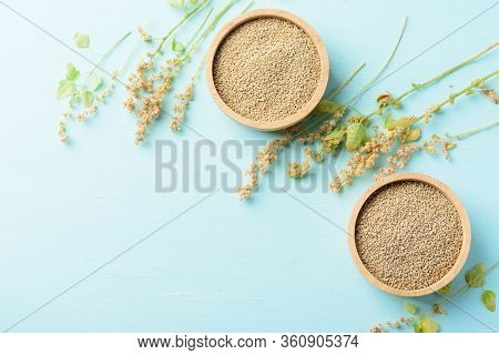Organic Brown Quinoa Seed In A Wooden Bowl And Quinoa Plant On Pastel Color Background, Healthy Food