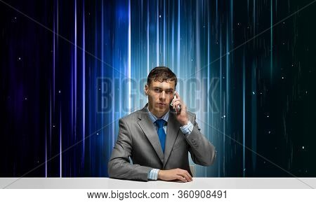 Internet Consultant Talking On Phone. Businessman Sitting At Desk On Abstract Matrix Like Background
