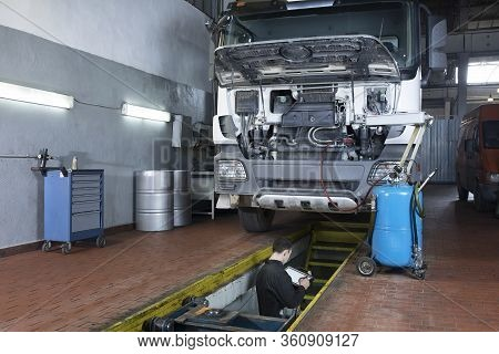Truck Under Repair In The Garage.  Mechanic Performs Computer Diagnostics.  Equipped Workplace.