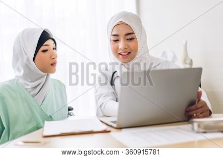 Muslim Asian Female Doctor Consulting And Check Up Information On Laptop Computer With Muslim Woman