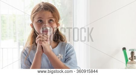 Cute Little Asian Girl With Oxygen Pipe And Using Oxygen Mask For Inhalations And Treatment On Her F