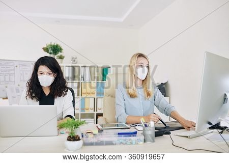 Team Of Female Graphic Designers In Medical Masks Sitting Next To Each Other At Office Desk When Wor