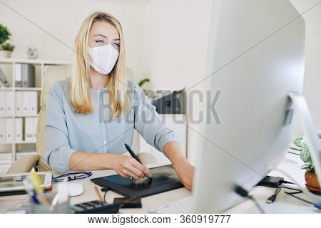 Young Female Graphic Designer With Medical Mask On Her Face Using Graphics Tablet While Working With