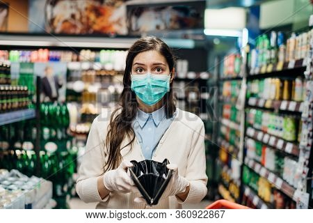 Stressed Woman With Mask Shopping In Grocery Store With An Empty Wallet.bankruptcy/recession.covid-1