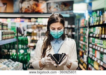 Worried Woman With Mask Groceries Shopping In Supermarket Looking At Empty Wallet.not Enough Money T