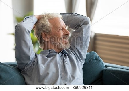 Smiling Older Man Relaxing On Couch, Dreaming, Looking Into Distance