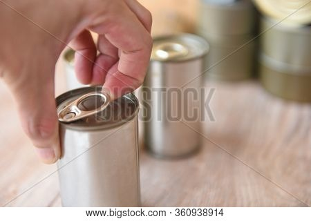 Hand Open Canned Food In Metal Can On Wooden Background / Close Up Canned Goods Non Perishable Food