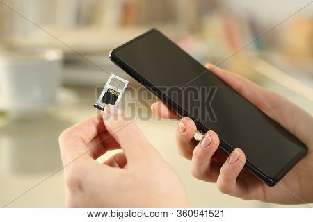 Close Up Of Girl Hand Inserting Sim And Sd Card On Smart Phone Sitting On A Desk At Home