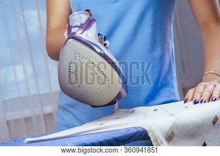 The Girl Irons The Iron Of Things On The Ironing Board. Cleaning Of The Apartment. Blue T-shirt And