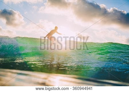 March 15, 2020. Bali, Indonesia. Surfer Man On Surfboard During Surfing. Surfer Ride On Ocean Wave.