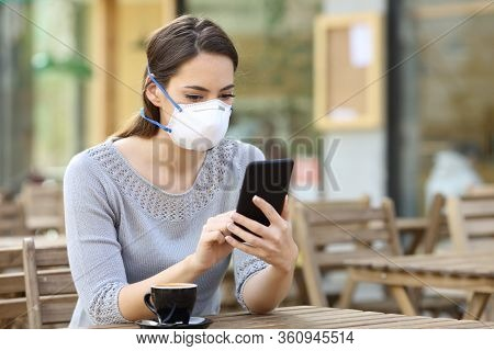 Serious Woman With Protective Mask Avoiding Contagion Checking News On Smart Phone On A Coffee Shop