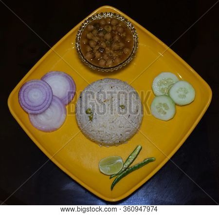 Authentic Indian Dish Chole Chawal (rice With Chickpea Gravy) Along With Sliced Onion, Cucumber, Lem