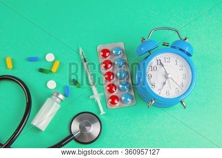 Studio Shot Of Stetoscope, Clock, Syringe And Pills On Light Green Background. Top Views.