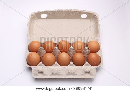 Ten Eggs Lie In A Cardboard Box On A White Background