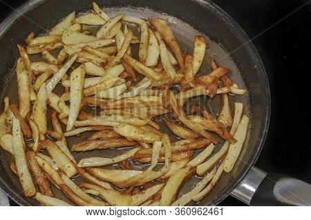 Frying French Fries In Hot Olive Oil At Home Kitchen Close Up. Top View Of Preparing Fresh Cut House