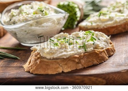 Slices Of Crusty Bread And A Glass Bowl With A Cream Cheese Spread And Cut Chives On A Vintage Woode