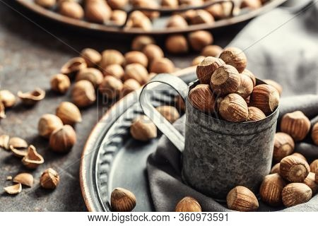 Hazelnuts And Their Cracked Shells On A Vintage Dark Metallic Background, In A Metallic Cup And On A