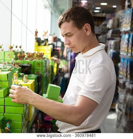 Tourist Chooses Souvenirs In The Store. Caucasian Tourist Buys Souvenirs Gifts From Vacation Relativ