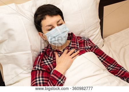 Sick Woman In Medical Mask Lying In Bed Feeling Chest Pain And Panting. Short-haired Brunette With S