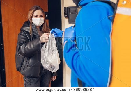 Contacless Delivery Service During Quarantine. Man Delivers Food And Shopping Bags During Isolation.