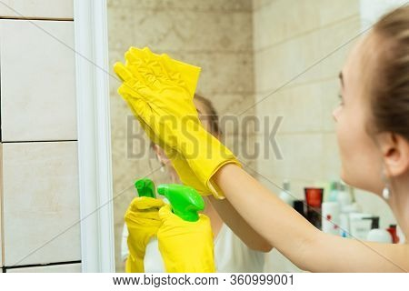 A Girl Is Washing A Mirror In Yellow Gloves. A Girl Is Cleaning A Mirror With Detergents.