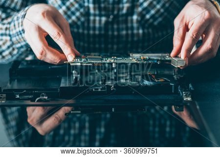 Electronic Engineering. Computer Maintenance. Male Technician Examining Disassembled Laptop.