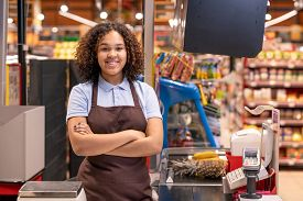 Pretty young smiling African-american female sales clerk with her arms crossed by chest looking at you by cash register during work