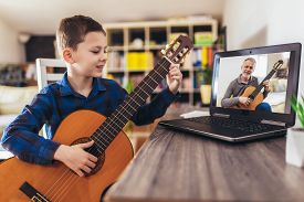 Focused Boy Playing Acoustic Guitar And Watching Online Course On Laptop While Practicing At Home. O