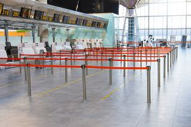 Empty Passenger Terminal At The Airport. Paths Limited And Separated By A Red Flight To The Check-in